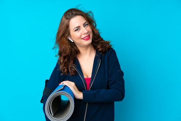 Giovane donna sportiva sopra isolato blu con una stuoia e sorridente