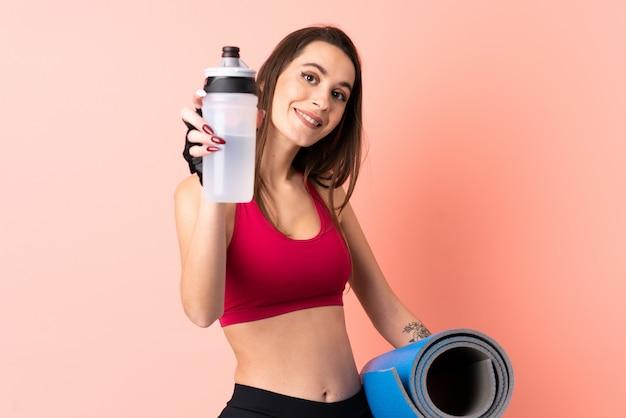 Giovane donna sportiva sopra la parete rosa isolata con la bottiglia di acqua di sport e con una stuoia