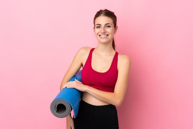 Giovane donna sportiva sopra la parete rosa isolata con una stuoia e sorridere