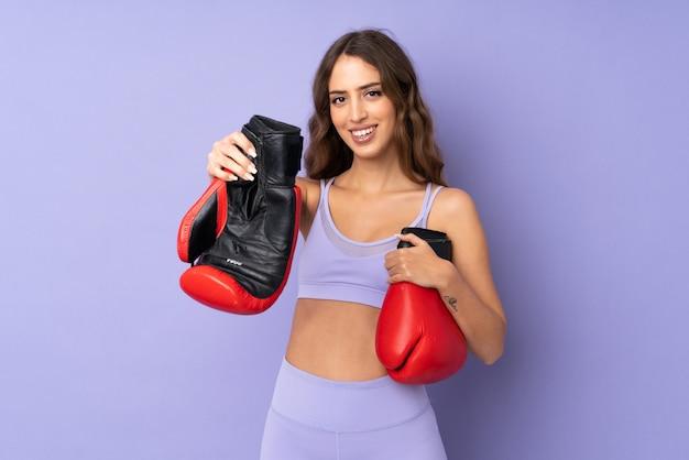 Giovane donna sportiva sopra la parete viola con guantoni da boxe