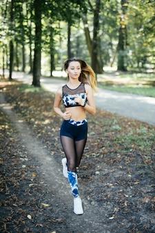 Giovane donna sportiva sorridente che corre all'aperto nel parco