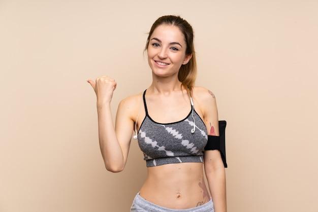 Giovane donna sportiva su sfondo isolato che punta al lato per presentare un prodotto