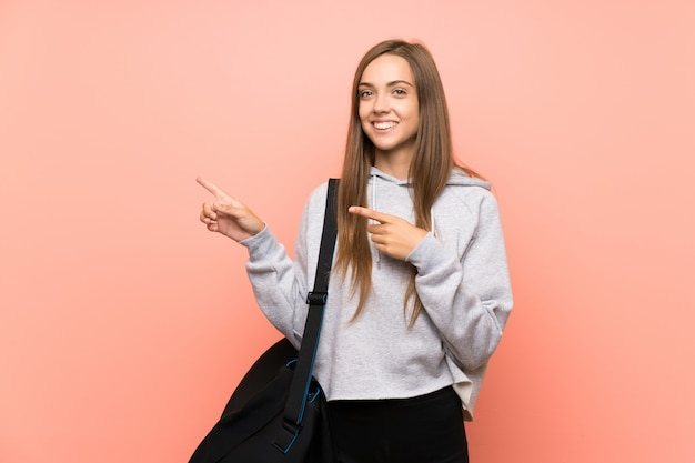 Giovane donna sportiva su sfondo rosa isolato che punta il dito verso il lato