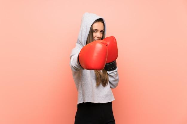 Giovane donna sportiva su sfondo rosa isolato con guantoni da boxe