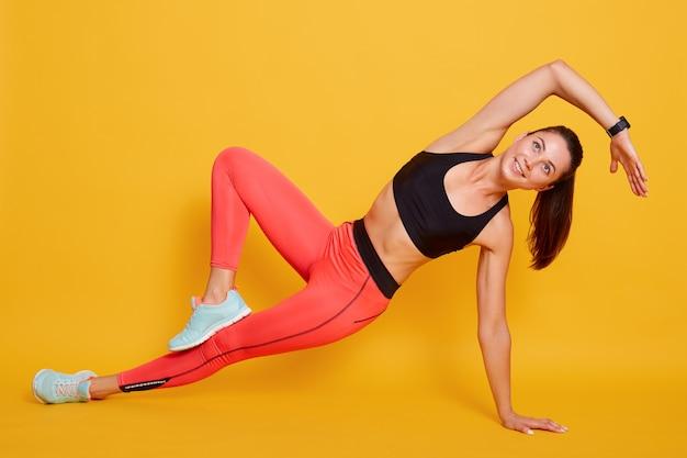 Giovane donna sportiva vicina che fa gli esercizi di sport isolati su giallo, indossando gli abiti sportivi alla moda. concetto di vita sana e naturale equilibrio tra corpo e sviluppo mentale.