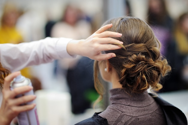 Giovane donna / sposa farsi i capelli prima del matrimonio o della festa