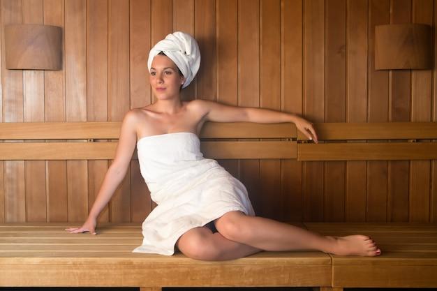 Giovane donna spugna rilassante sulla panchina nella sauna