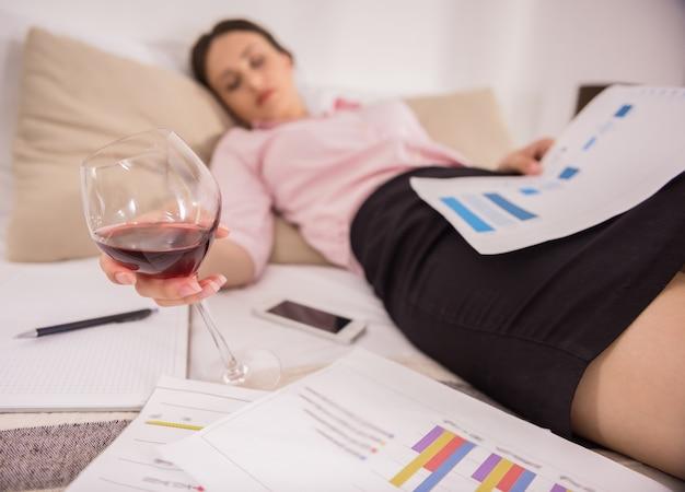 Giovane donna stanca che dorme sul letto con bicchiere di vino.