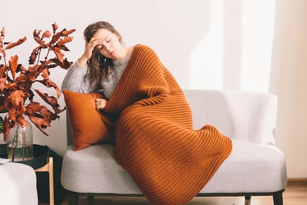 Giovane donna stanca che si trova sul sofà sul fondo bianco della parete. mal di testa.