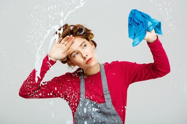 Giovane donna stanca stanca delle funzioni domestiche mentre pulendo