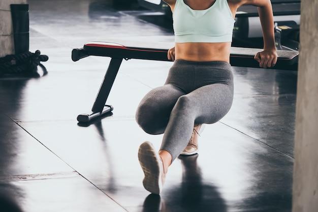 Giovane donna stretching e riscaldamento prima dell'allenamento in palestra