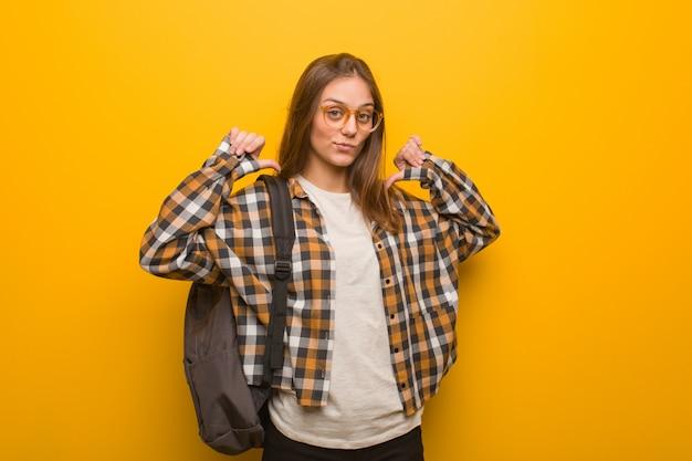 Giovane donna studente che punta le dita, esempio da seguire