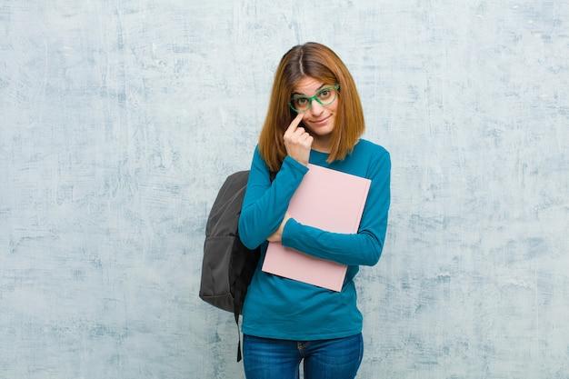 Giovane donna studentessa che ti tiene d'occhio, non fidandosi, guardando e rimanendo vigile e vigile