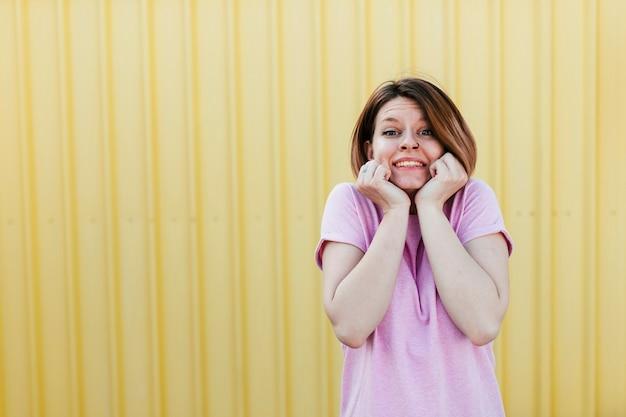 Giovane donna stupita che si leva in piedi contro il contesto giallo del ferro ondulato