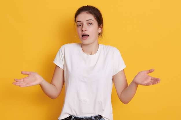 Giovane donna stupita del brunette che spande le palme da parte, scrollando le spalle le spalle