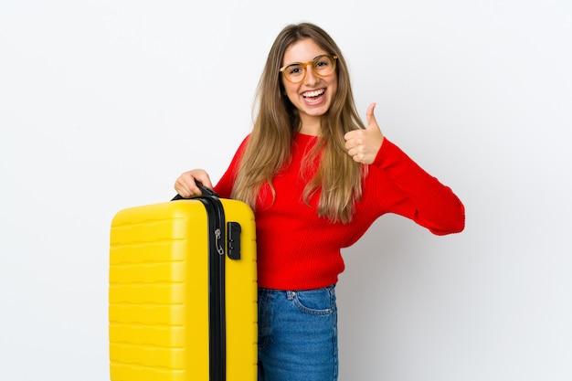 Giovane donna su bianco isolato in vacanza con la valigia di viaggio e con il pollice in su