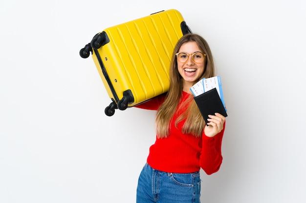 Giovane donna su bianco isolato in vacanza con la valigia e il passaporto