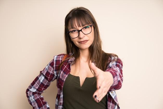 Giovane donna su handshaking di sfondo ocra dopo un buon affare