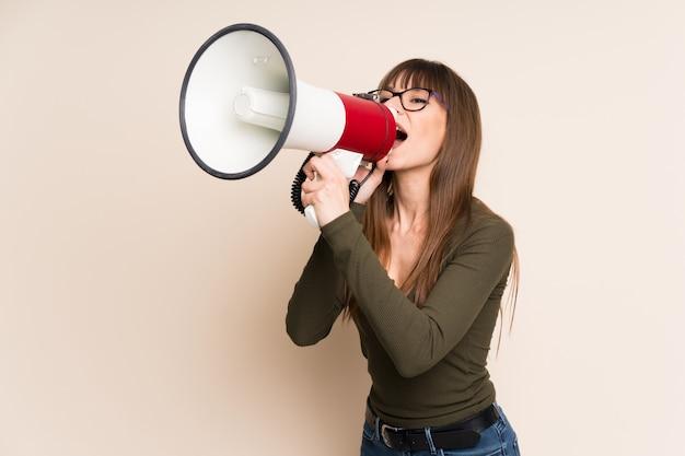 Giovane donna su ocra che grida attraverso un megafono