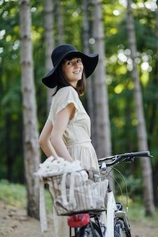 Giovane donna su sfondo di natura con bici
