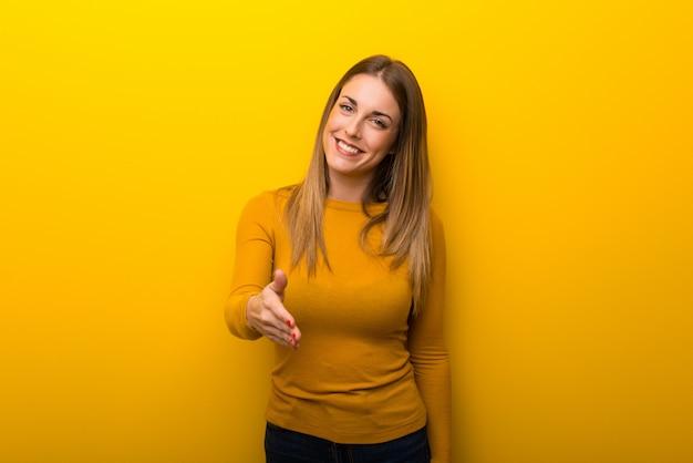 Giovane donna su sfondo giallo, agitando le mani per la chiusura di un buon affare