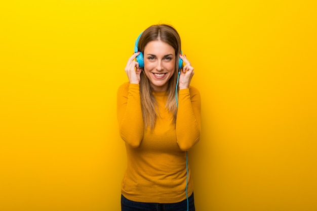 Giovane donna su sfondo giallo, ascoltando musica con le cuffie