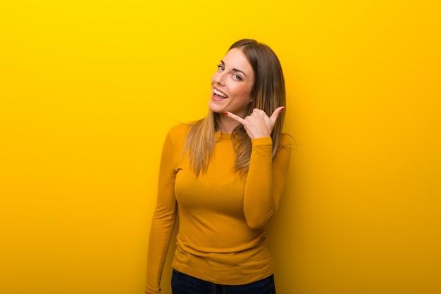 Giovane donna su sfondo giallo che fa gesto di telefono. chiamami segno
