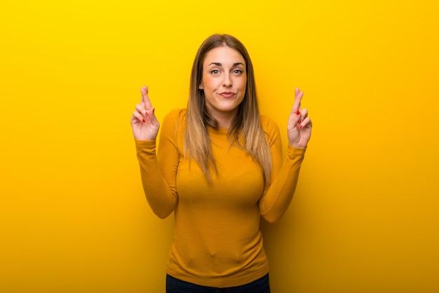 Giovane donna su sfondo giallo con le dita che attraversano e che desiderano il meglio