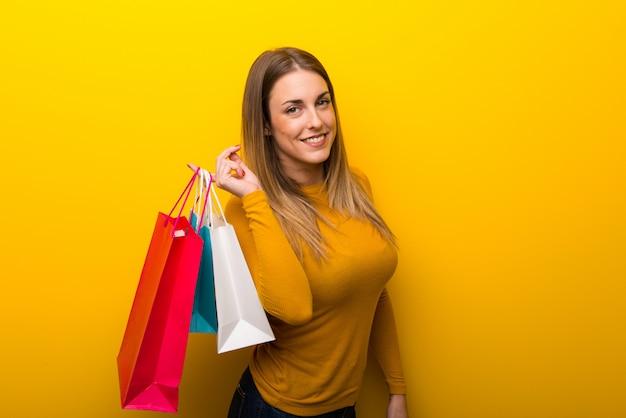 Giovane donna su sfondo giallo in possesso di un sacco di borse per la spesa