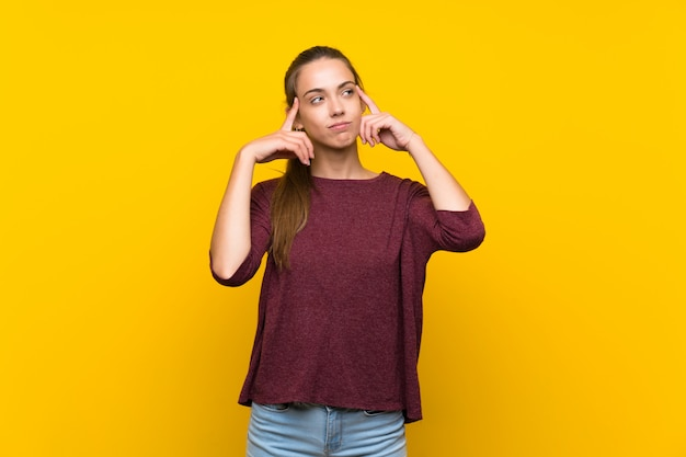 Giovane donna su sfondo giallo isolato avendo dubbi e pensando