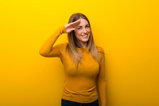 Giovane donna su sfondo giallo salutando con la mano