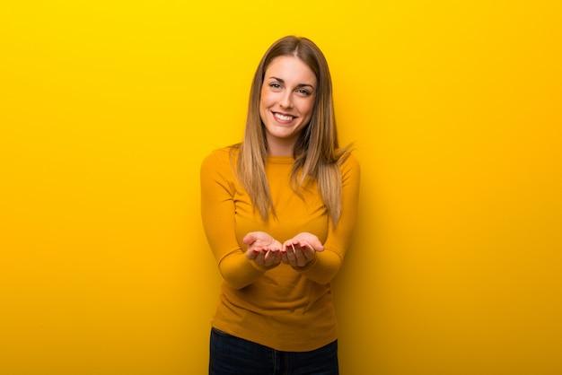 Giovane donna su sfondo giallo tenendo copyspace immaginario sul palmo per inserire un annuncio