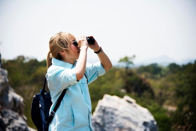 Giovane donna su una montagna con il binocolo