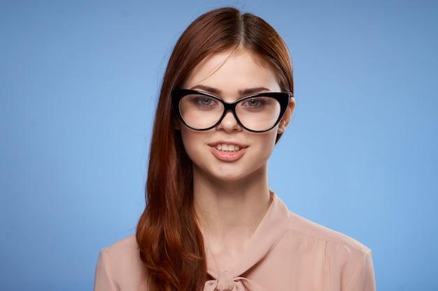 Giovane donna su una parete blu con occhiali in posa, emozioni diverse, modello