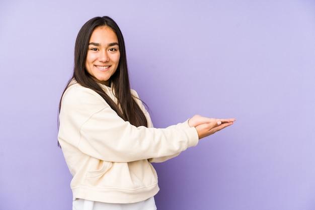 Giovane donna su una parete viola in possesso di uno spazio vuoto su una palma.