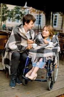 Giovane donna su una sedia a rotelle, bere il caffè in un bar all'aperto con suo marito e divertirsi.