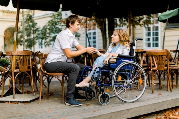 Giovane donna su una sedia a rotelle godendo una buona compagnia in una data con il suo bell'uomo in un bar all'aperto in città
