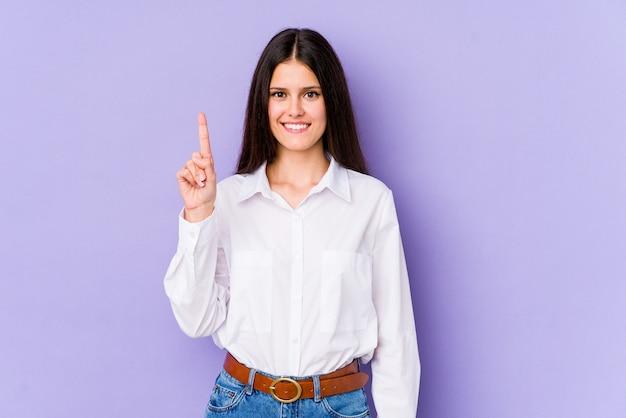 Giovane donna su viola mostrando il numero uno con il dito.