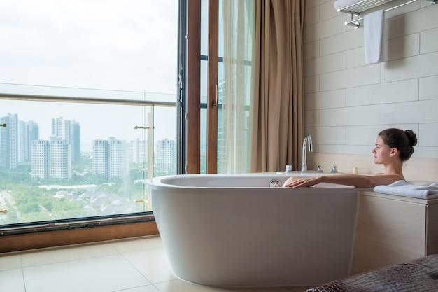 Giovane donna sul bagno bianco nel bagno di lusso con vista sulla città