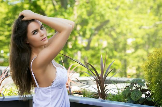 Giovane donna sul balcone al mattino
