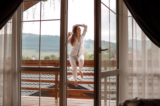 Giovane donna sul balcone che tiene una tazza di caffè o tè al mattino. lei nella camera d'albergo guarda la natura in sumer. la ragazza è vestita in indumenti da notte alla moda. tempo di relax.