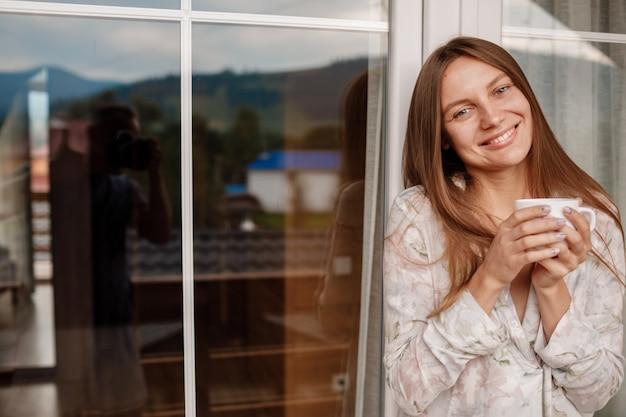 Giovane donna sul balcone che tiene una tazza di caffè o un tè al mattino. la donna è vestita con indumenti da notte eleganti. tempo di relax.