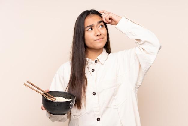 Giovane donna sul beige che ha dubbi e con espressione del viso confuso mentre si tiene una ciotola di noodles con le bacchette