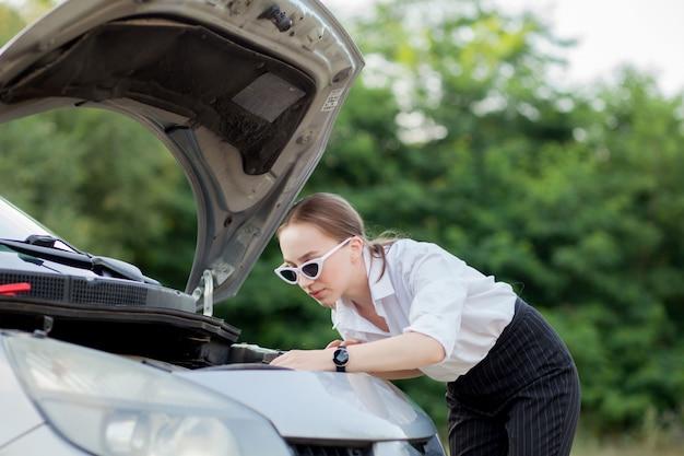 Giovane donna sul ciglio della strada dopo che la sua macchina si è rotta ha aperto il cofano per vedere il danno