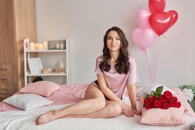 Giovane donna sul letto in pigiama rosa con bouquet di rose rosse
