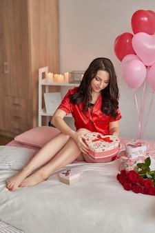 Giovane donna sul letto in pigiama rosso con scatola regalo a forma di cuore