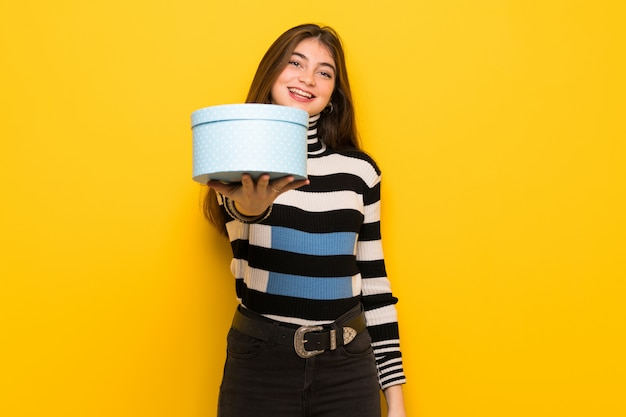 Giovane donna sul muro giallo con un regalo in mano