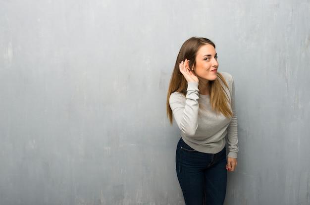 Giovane donna sulla parete strutturata ascoltando qualcosa mettendo la mano sull'orecchio