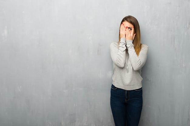 Giovane donna sulla parete strutturata che copre gli occhi con le mani e guardando attraverso le dita