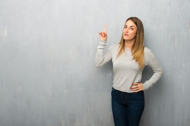 Giovane donna sulla parete strutturata che mostra e che alza un dito nel segno del meglio